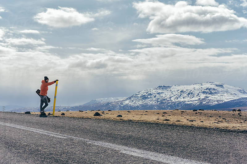 Man looking at view on the road holding his skateboard in Iceland by Søren Egeberg Photography for Stocksy United