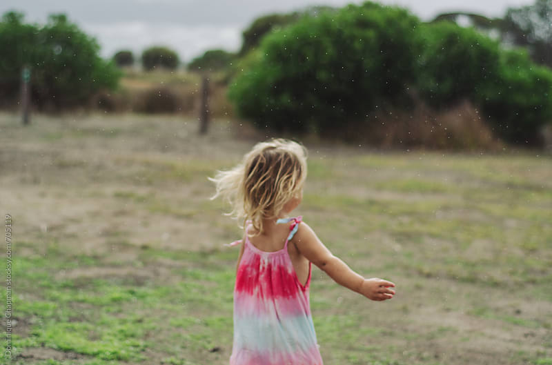 Little girl running free in the rain by Dominique Chapman for Stocksy United