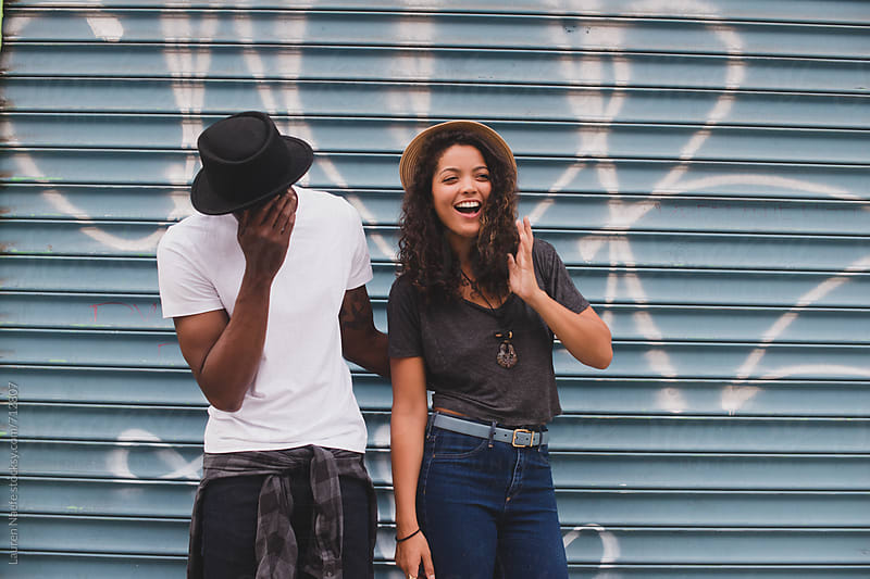 Hapy young couple laughing, hanging out in the city by Lauren Naefe for Stocksy United