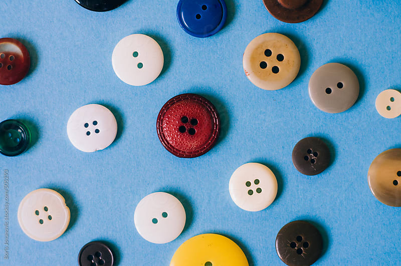 Colorful buttons on blue background by Boris Jovanovic for Stocksy United