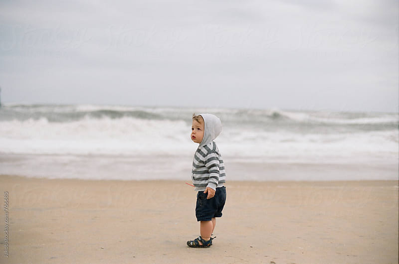 Cute young boy standing alone on a beach with ocean behind him by Jakob for Stocksy United