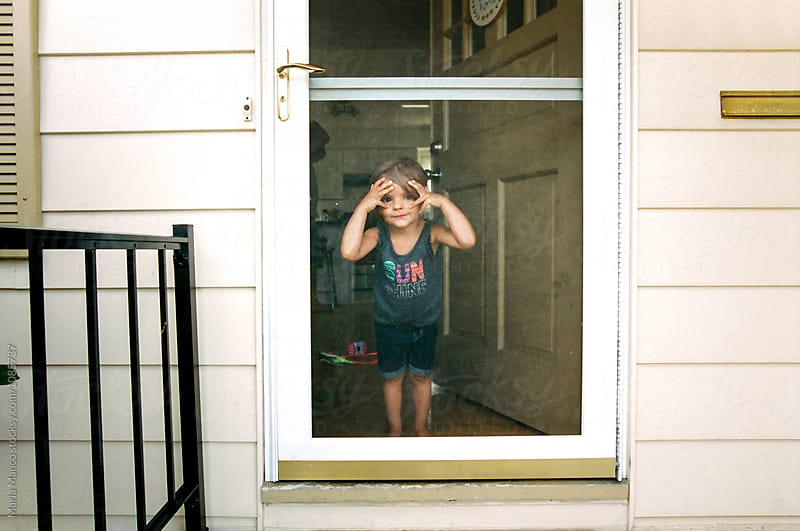 little girl looks out door by Maria Manco for Stocksy United