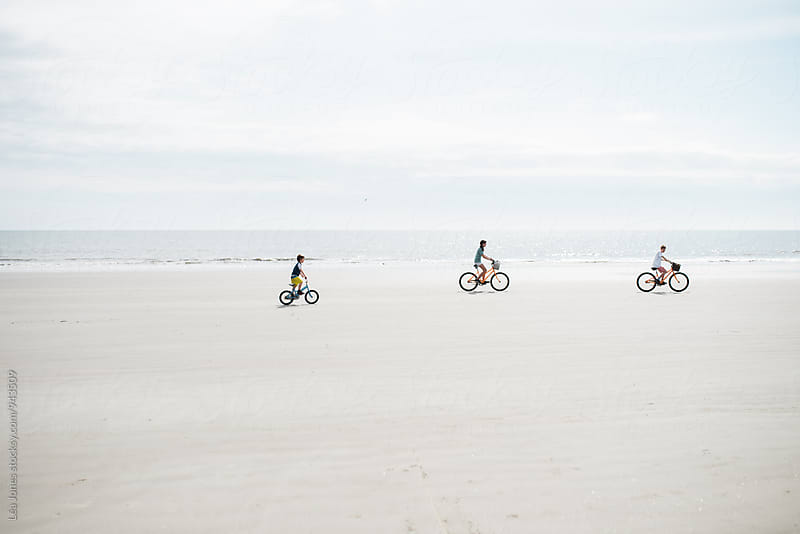 three kids biking on the beach by Léa Jones for Stocksy United