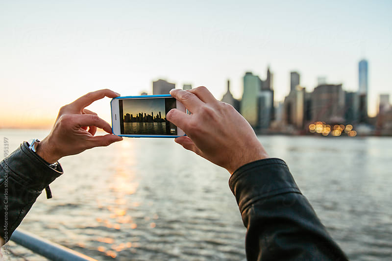 Hands of a man taking a photo with a phone to city skyline at sunset by Alejandro Moreno de Carlos for Stocksy United