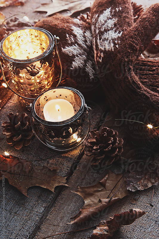 Candles, winter mittens and leaves on table by Sandra Cunningham for Stocksy United