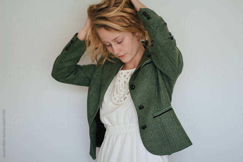 Girl with Blonde Hair Modelling a Green Jacket and a Summer Dress by Jacqui Miller for Stocksy United