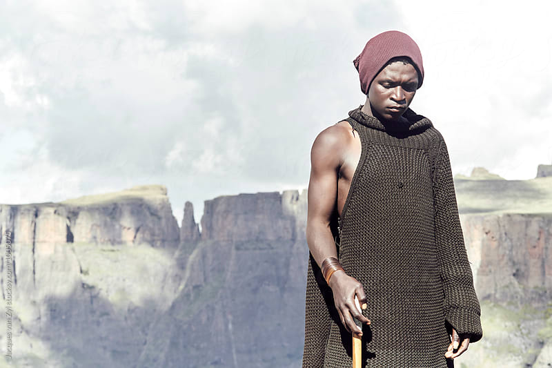 An epic portrait of a Bashoto shepherd standing in front of wild mountains.  by Jacques van Zyl for Stocksy United
