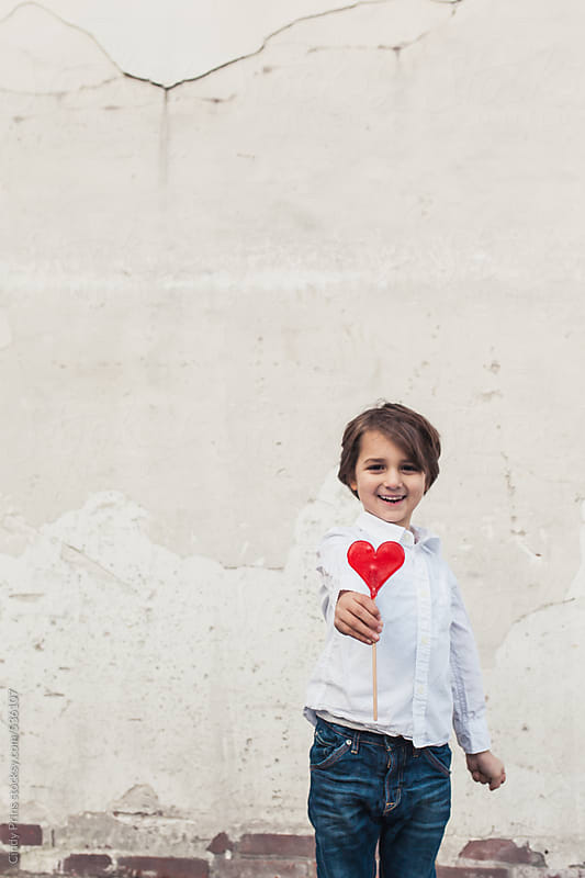 Little boy holding a red lollipop heart by Cindy Prins for Stocksy United