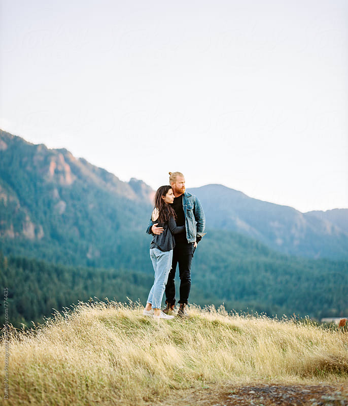 Young couple embracing on mountain by Daniel Kim Photography for Stocksy United
