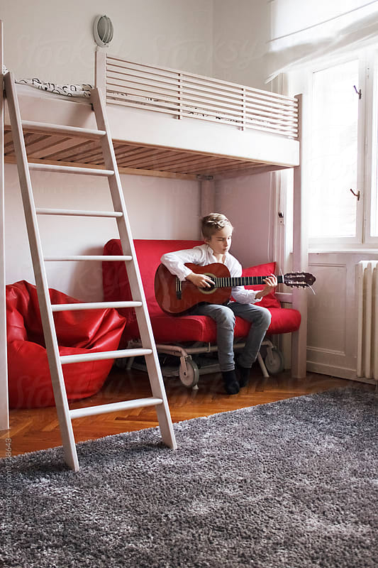 Little boy playing a guitar in his room by Jovana Rikalo for Stocksy United
