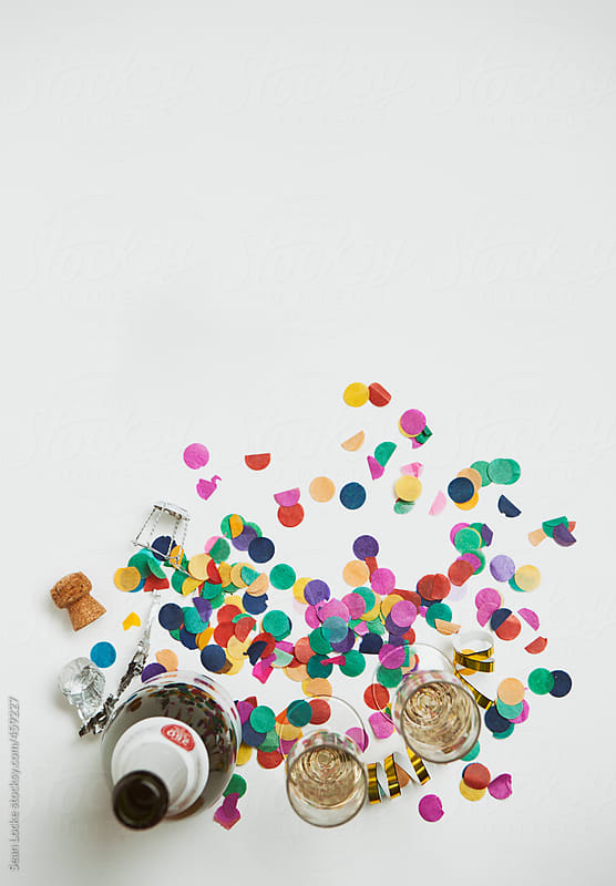 NYE: Champagne Bottle And Glasses Sit In Confetti by Sean Locke for Stocksy United