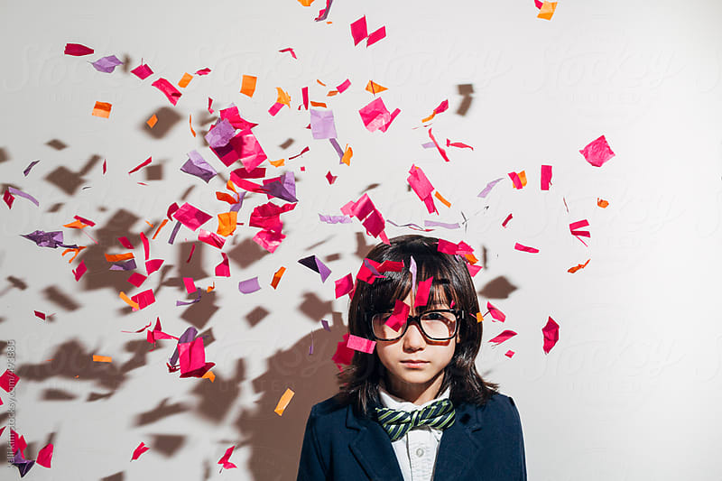Serious young boy with confetti all around him by Kelli Seeger Kim for Stocksy United