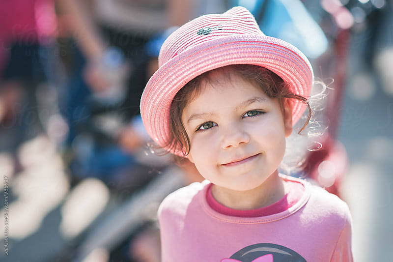 Portrait of a cute little girl wearing a pink hat by Lea Csontos for Stocksy United