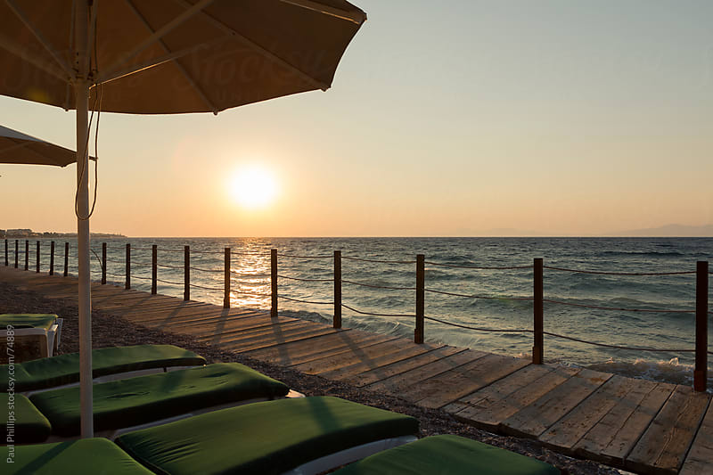 Sunbeds, sea and sunset, Rhodes, Greece by Paul Phillips for Stocksy United