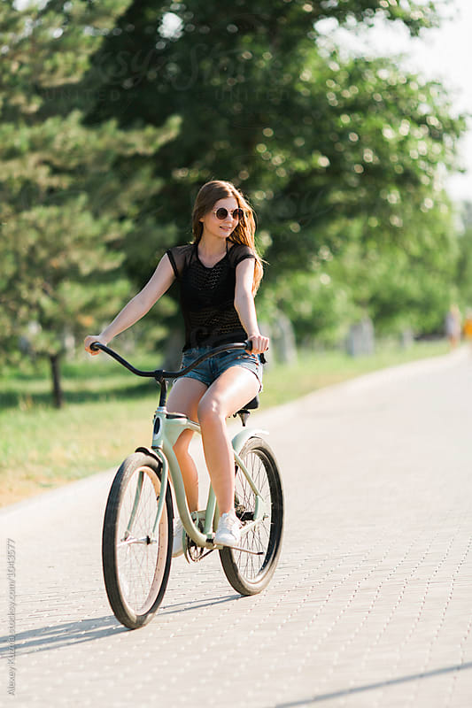 Happy Young Woman Riding a Bike . by Alexey Kuzma for Stocksy United