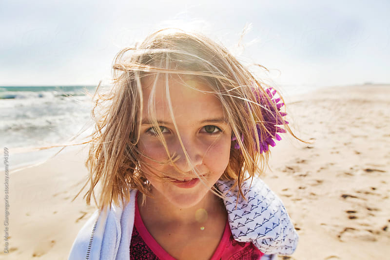 Wide angle headshot of pre-teen girl on beach with wind in hair by Dina Giangregorio for Stocksy United
