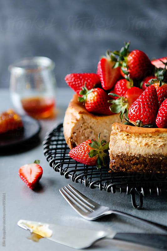 Honey cheesecake topped with strawberries by Ellie Baygulov for Stocksy United
