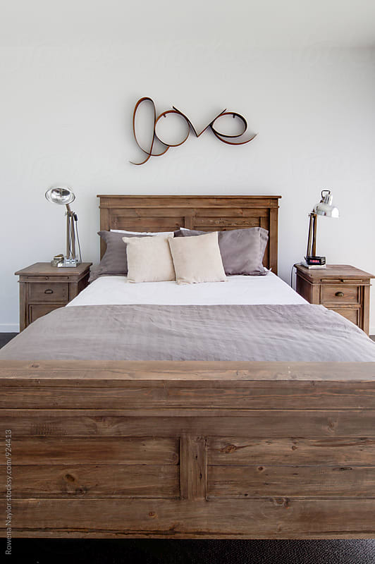 Bedroom with LOVE written above bed by Rowena Naylor for Stocksy United