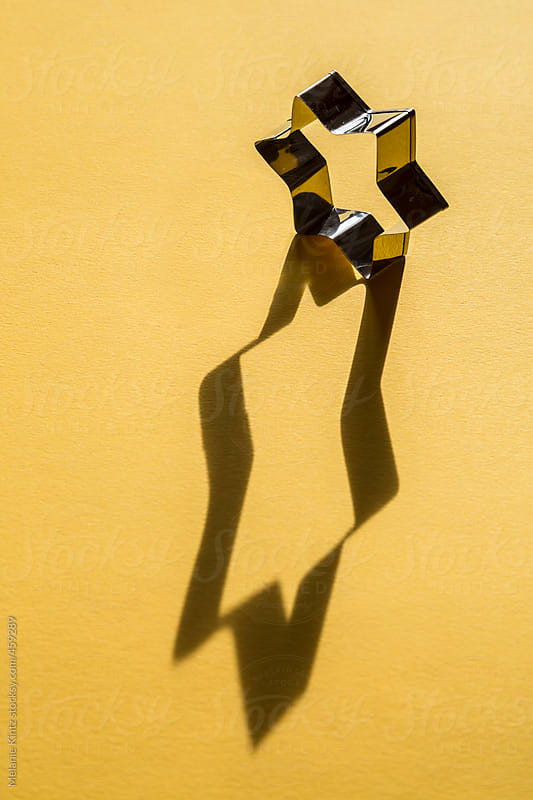 star shaped cookie cutter casts a long shadow on yellow background by Melanie Kintz for Stocksy United