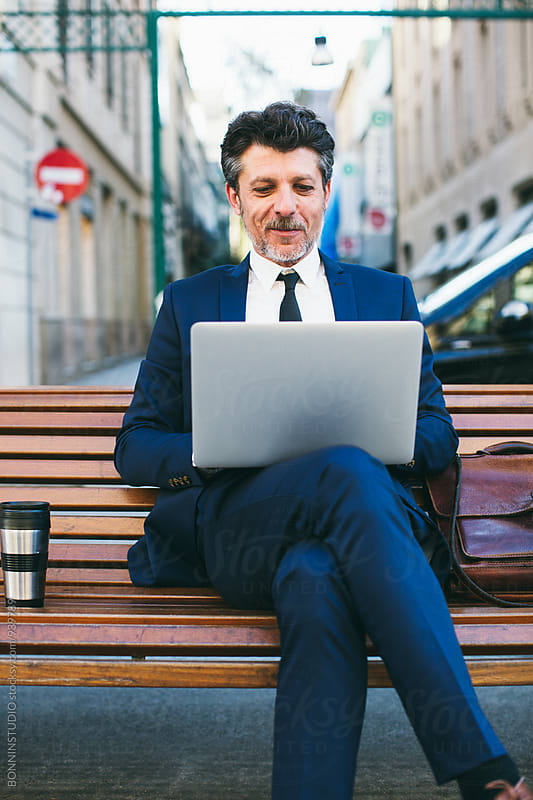 Mature businessman sitting on a bench working on his laptop. by BONNINSTUDIO for Stocksy United
