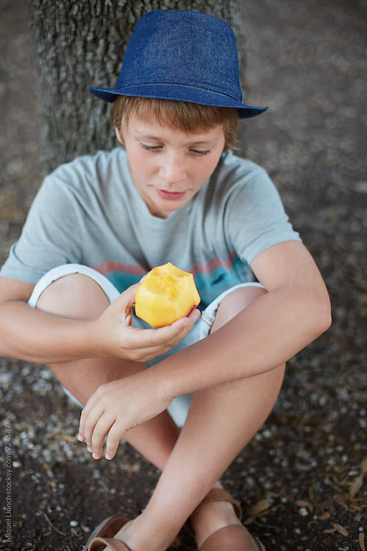 Young man eating a peach in the yard by Miquel Llonch for Stocksy United