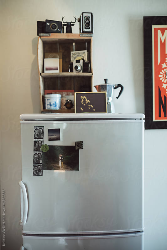 A tiny refrigerator with knick knacks and pictures on it  by Kristine Weilert for Stocksy United