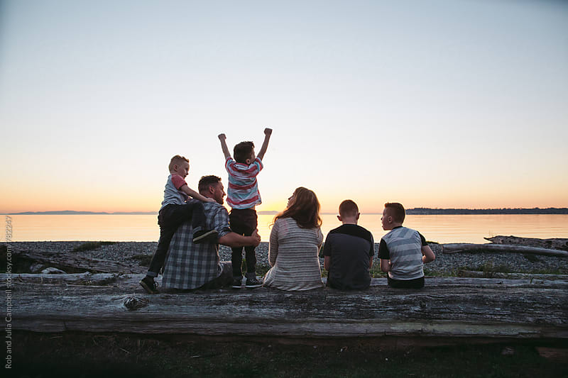 Young family having fun together outside - looking at sunset - shot from behind by Rob and Julia Campbell for Stocksy United