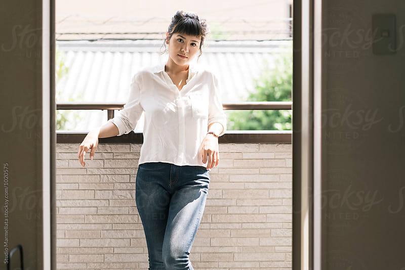 Attractive asian woman enjoying sun light on the balcony by Juri Pozzi for Stocksy United