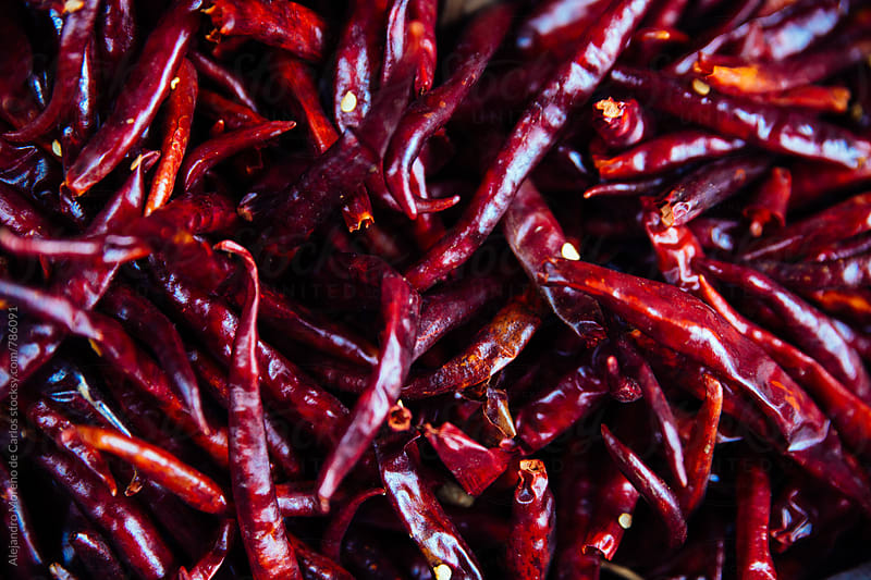 Background of many red spicy chili peppers stacked together by Alejandro Moreno de Carlos for Stocksy United