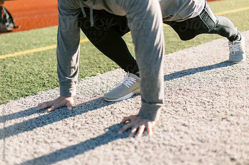 Athletic Man Stretching Legs Before Workout At Track And Field by Luke Mattson for Stocksy United