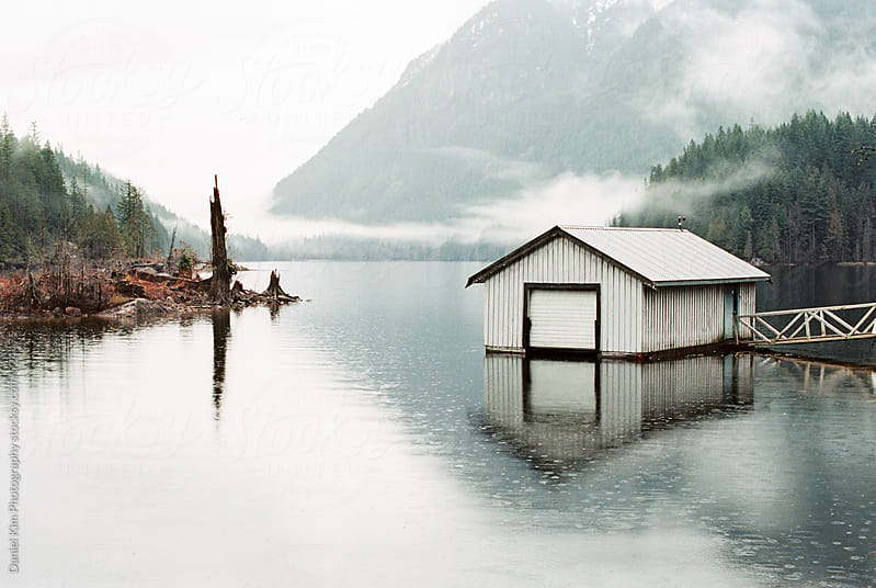 Boathouse on overcast lake by Daniel Kim Photography for Stocksy United