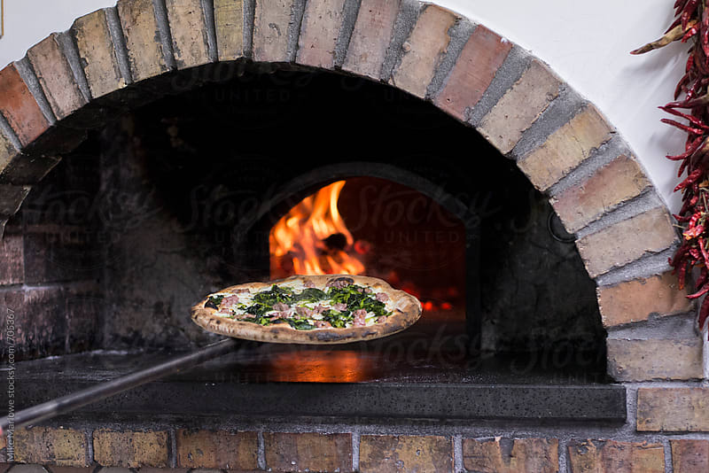 A pizza being put in to a wood fired oven for cooking by Mike Marlowe for Stocksy United