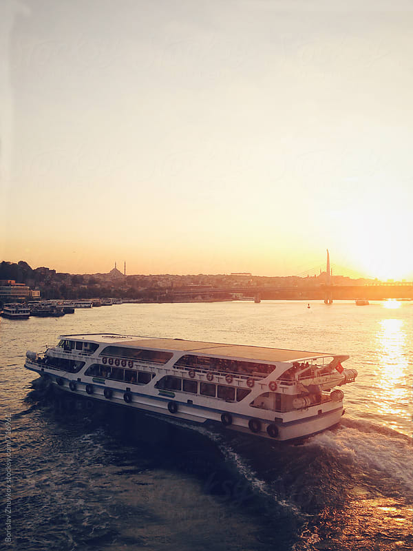 Ferry crossing Golden Horn with silhouette of Eyup Sultan mosque behind at dusk by Borislav Zhuykov for Stocksy United