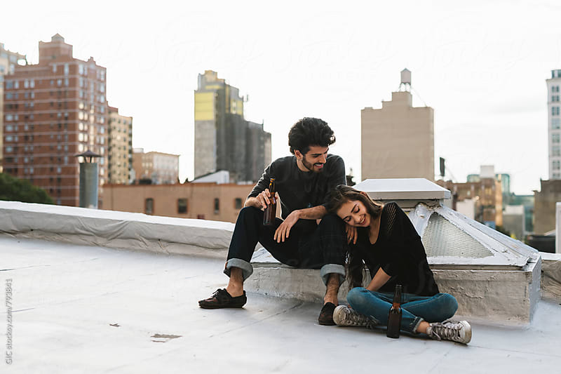 Young couple having fun on a rooftop in the city by GIC for Stocksy United