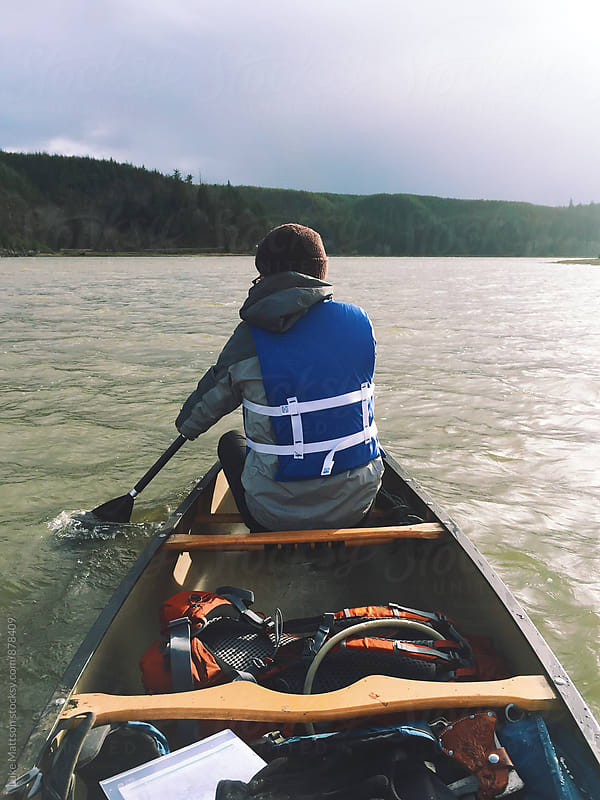 Young Man Paddling In Bow Of Canoe Filled With Backpacking Gear by Luke Mattson for Stocksy United