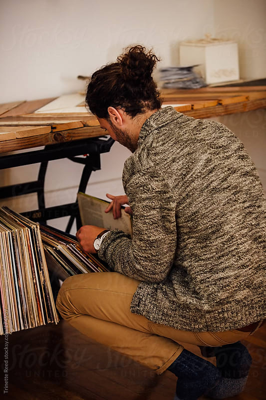 Man looking through record albums at home by Trinette Reed for Stocksy United