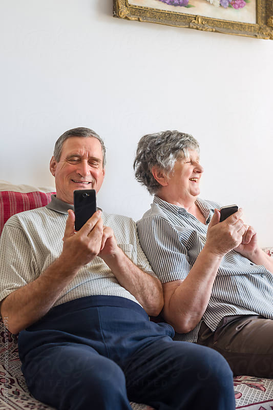 Senior couple having fun using smartphones by RG&B Images for Stocksy United