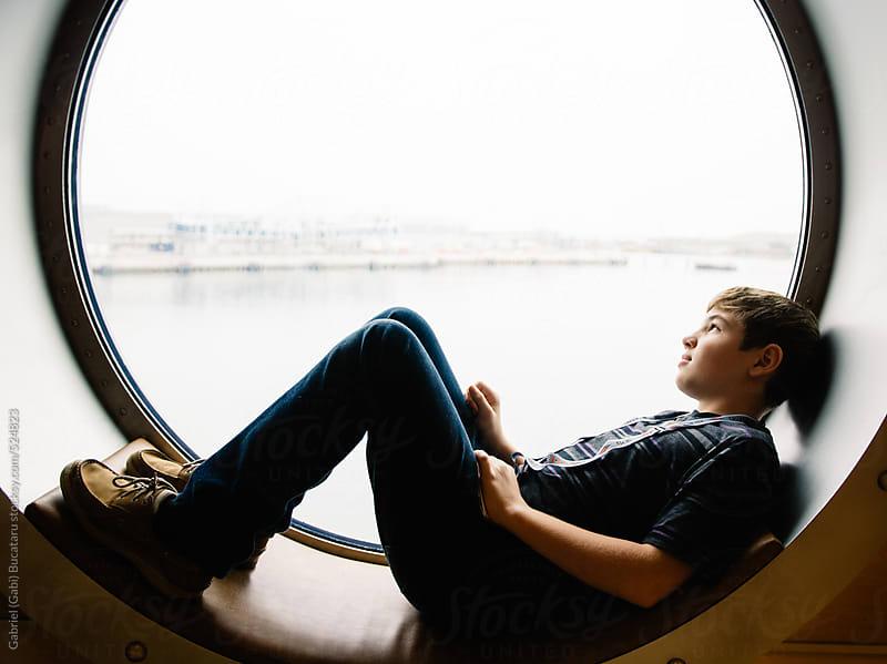 Boy laying by a cruise ship window by Gabriel (Gabi) Bucataru for Stocksy United