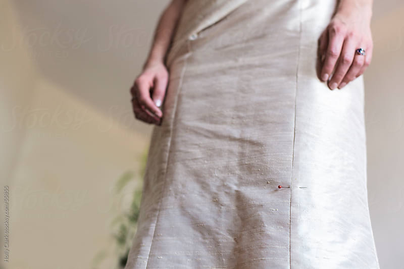The skirt of a gold dress with a pin holding together a seam. by Holly Clark for Stocksy United
