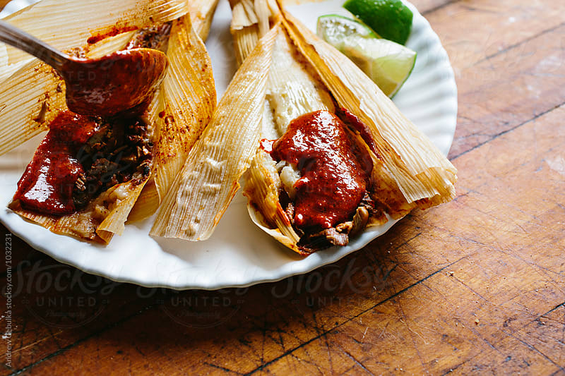 tamales in corn husks with lime and red sauce by Andrew Cebulka for Stocksy United
