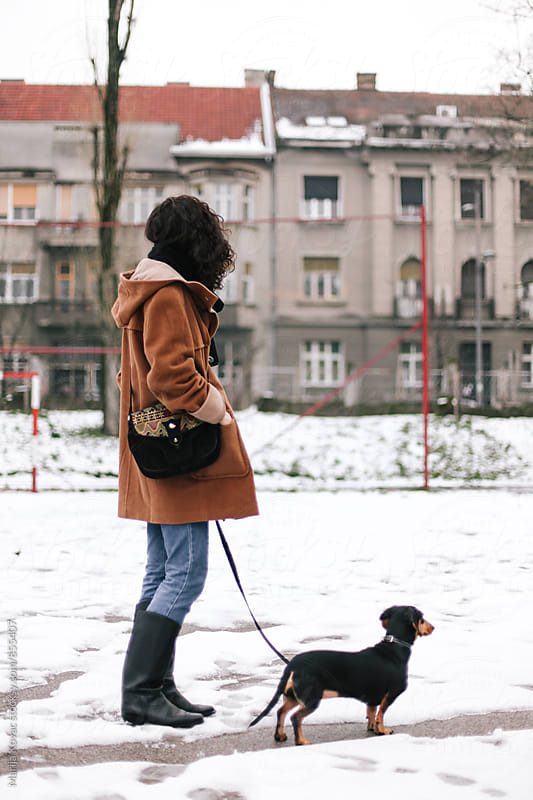 Stylish woman holding her black dog, outdoor  by Marija Kovac for Stocksy United