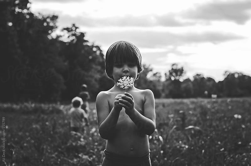 A Boy holds a White Flower by Ali Deck for Stocksy United