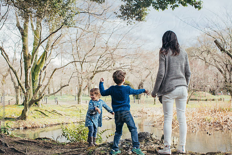 Family Outing - Two Children Throwing Stones into Lake with Their Mother by VISUALSPECTRUM for Stocksy United
