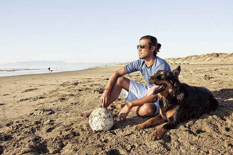 Mexican-American Young Man and His Dog at the Beach by Joselito Briones for Stocksy United