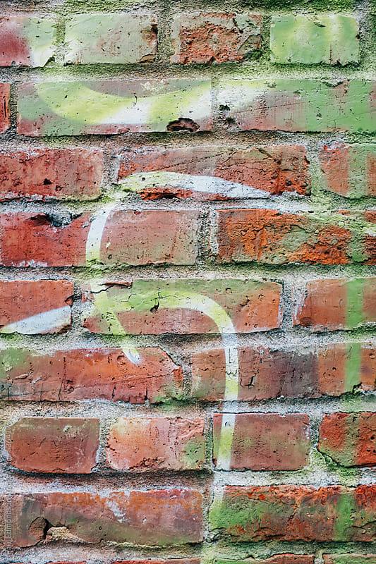 Graffiti markings on old brick wall by Paul Edmondson for Stocksy United