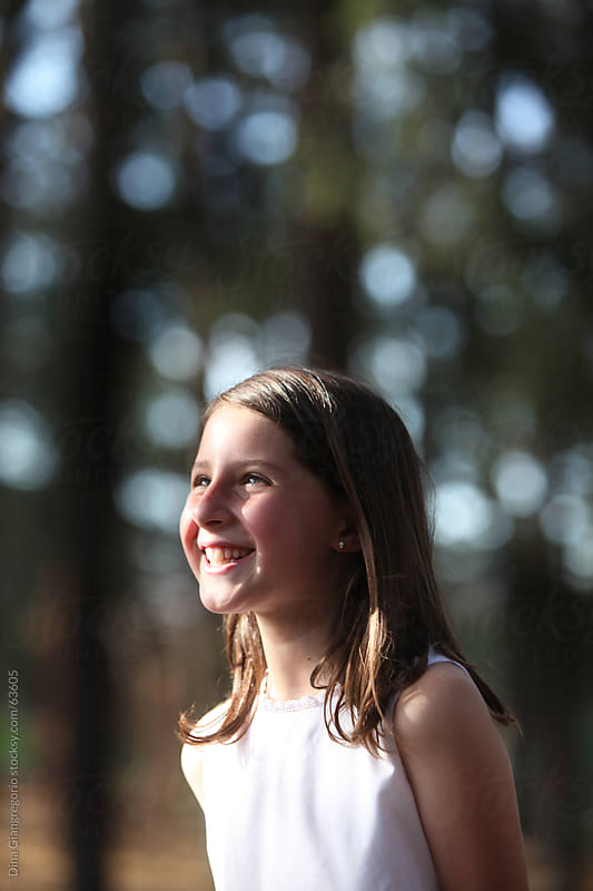 Side view of young girl in white dress standing in woods and smiling by Dina Giangregorio for Stocksy United
