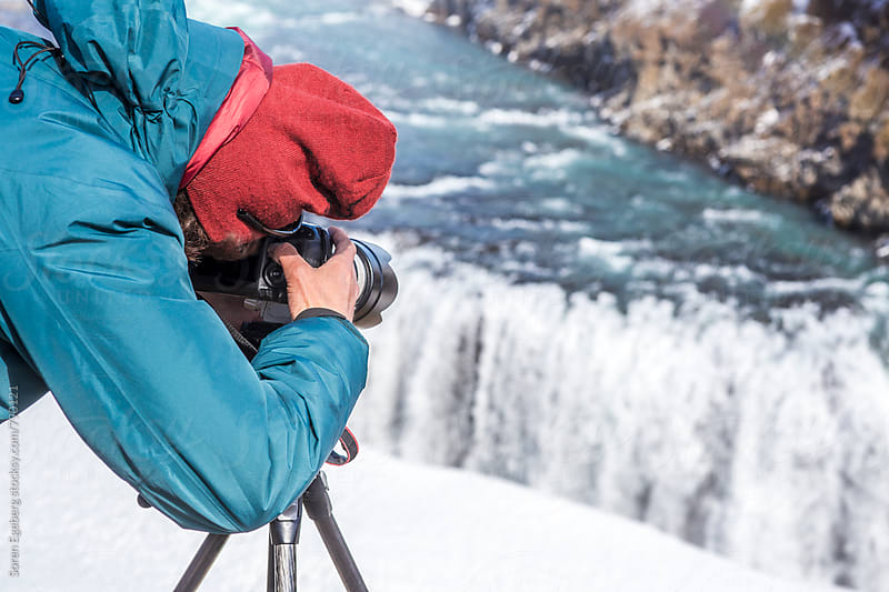 Man taking photos of Gullfoss waterfall in Iceland by Soren Egeberg for Stocksy United