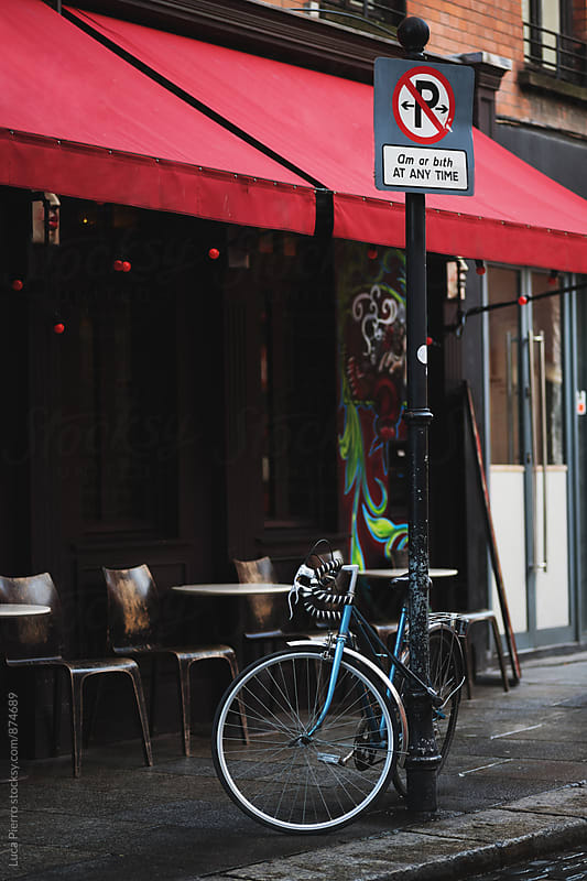 Parked bike outside a restaurant by Luca Pierro for Stocksy United