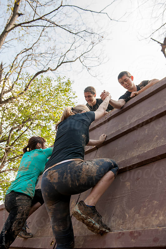 Competitors Help Each Other Over Climbing Obstacle on Mud Run by Brian McEntire for Stocksy United