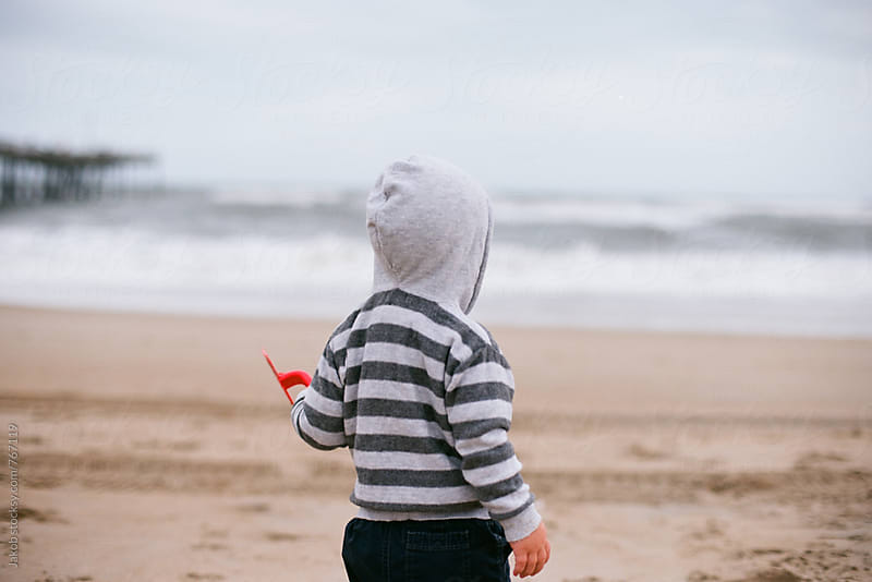 ute young boy with hoodie playing on the beach with a shovel by Jakob for Stocksy United